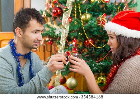 Young couple celebrating Christmas at home with glasses of wine , New Year's Eve of two beautiful people drinking wine beside Xmas tree - stock photo