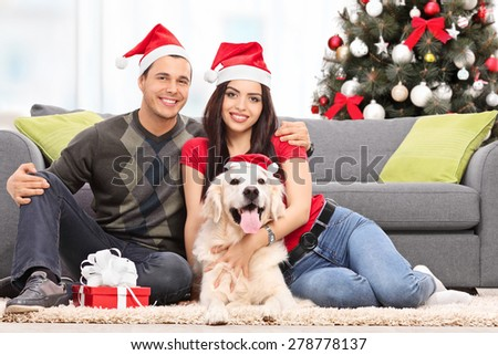 Young couple celebrating Christmas with their dog seated on the floor next to a modern sofa at their home
