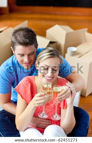 Young couple celebrating their removal with champagne sitting on the floor in their new house - stock photo