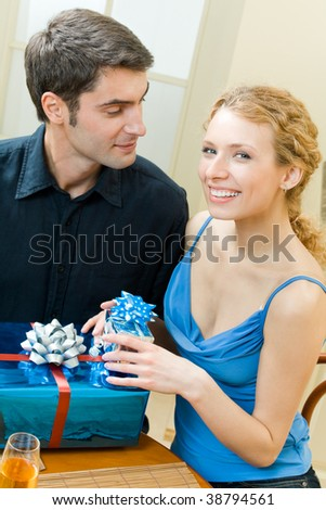 Young couple celebrating with champagne and gifts at home