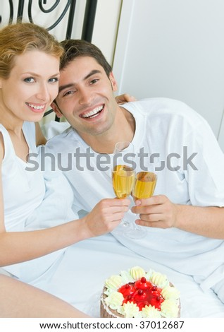 Young couple celebrating with champagne at bedroom