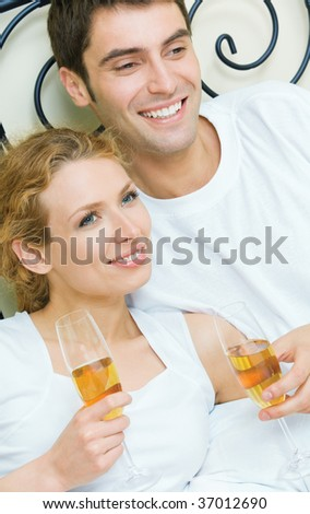 Young couple celebrating with champagne at bedroom - stock photo