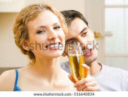 Young couple celebrating with champagne at home. Love, relations, romantic concept shoot.