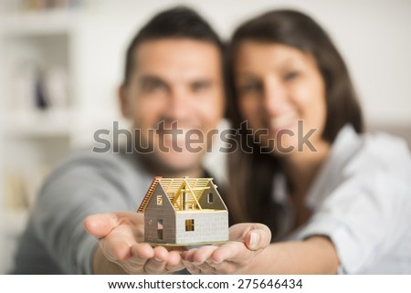 young couple checking blueprints of they new house