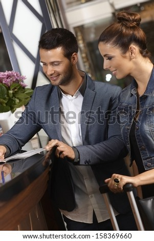 Young couple checking in at hotel reception upon arrival. - stock photo