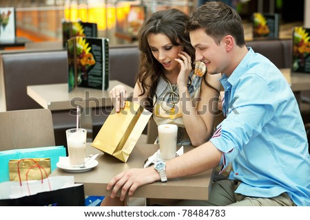 Young couple checking their shopping bags - stock photo