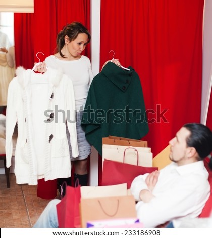 Young couple choosing coat in fitting-room at market - stock photo
