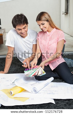 Young couple choosing colors from swatches while sitting on rug with blueprints - stock photo