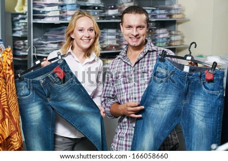 Young couple choosing jeans during clothing shopping at sales store - stock photo