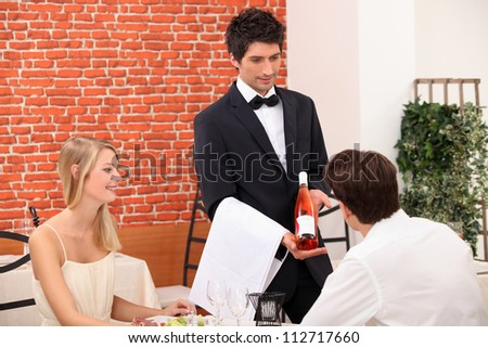 Young couple choosing rose wine in a restaurant - stock photo
