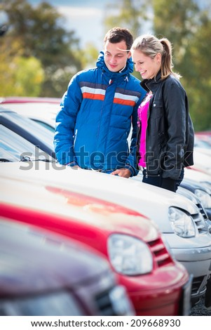 Young couple choosing the right car for them - stock photo