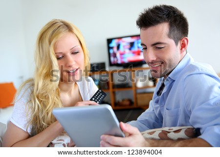 Young couple choosing tv program on internet - stock photo