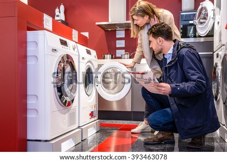 Young couple choosing washing machine in household appliance section at hypermarket - stock photo