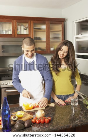Young couple chopping vegetables