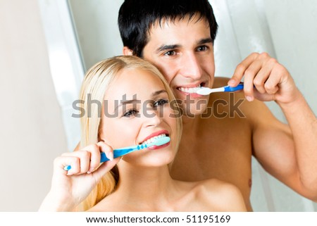 Young couple cleaning teeth together at bathroom - stock photo