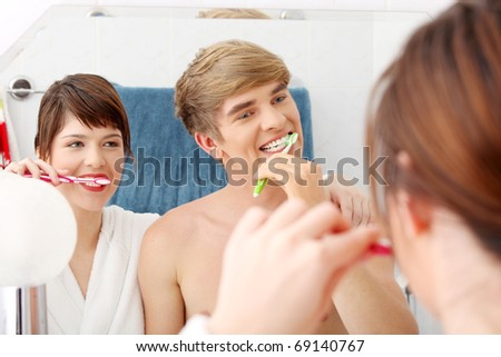 Young couple cleaning teeth together at bathroom. Focus on man.