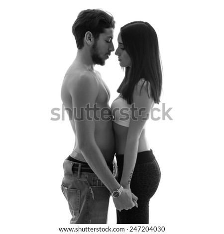 Young couple close up intimate studio portrait in a romantic mood. Black and white image. - stock photo