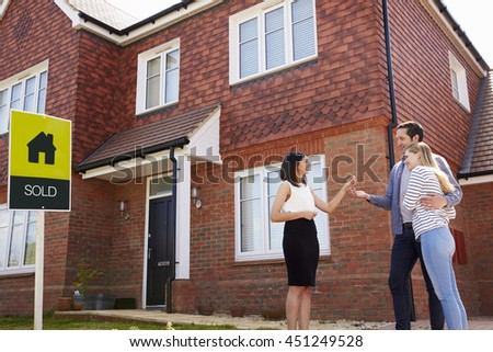 Young Couple Collecting Keys To New Home From Realtor - stock photo