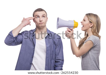 Young couple conflict concept. A woman screaming at a man through a megaphone. isolated on white background. - stock photo