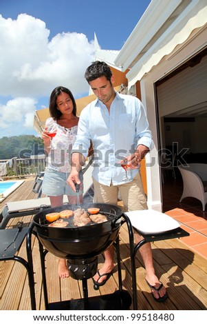 Young couple cooking dinner on barbecue grill - stock photo