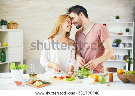 Young couple cooking fresh vegetarian salad together - stock photo