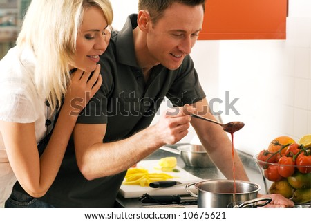 Young couple cooking (in this case: strawberry sauce for dessert) - stock photo