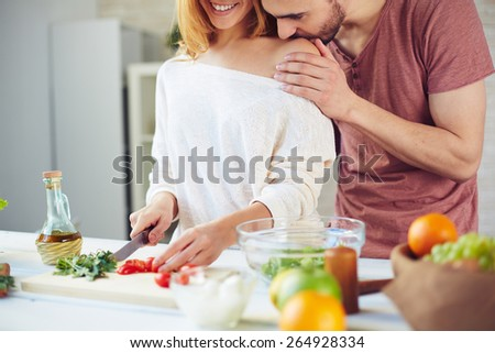 Young couple cooking salad for breakfast - stock photo