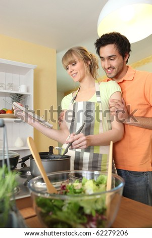 Young couple cooking with cookbook