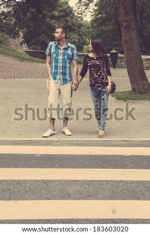 Young Couple Crossing Road on Zebra