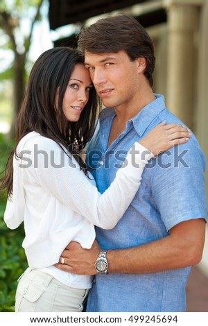 Young Couple Cuddling near Stores