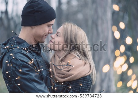 Young couple cuddling outdoor with christmas lights