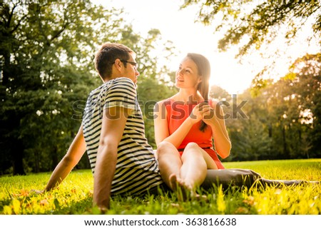 Young couple dating and hugging in nature - shot against direct sun - stock photo