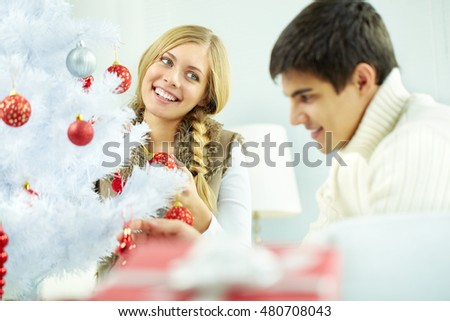 Young couple decorating Christmas tree before the celebration