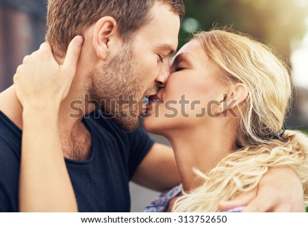 Young couple deeply in love sharing a romantic kiss, closeup profile view of their faces - stock photo