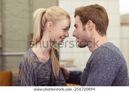Young couple deeply in love sharing a tender moment as they stand close together looking deeply into each others eyes, head and shoulders indoors at home - stock photo