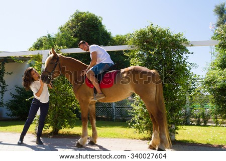 Young couple demonstrating their affection and warm feelings to their best friend brown-blond purebred mare, tenderly hugging, fondling, and kissing her. - stock photo