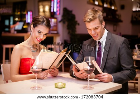 young couple dining in restaurant and reading menu. - stock photo