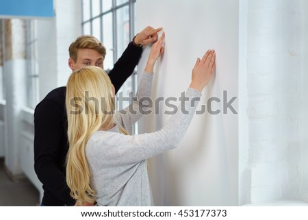 Young couple discussing interior renovations pointing to a white wall in a new apartment as they decide what furnishing should be placed there