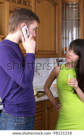 Young couple discussing something at home kitchen - stock photo