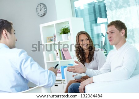 Young couple discussing their actuarial plan with an insurance broker - stock photo