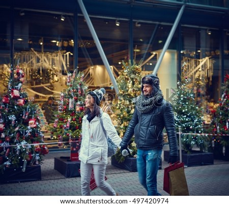 Young couple doing christmas shopping in the city, smiling, walking hand in hand.