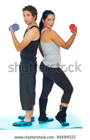 Young couple doing fitness exercises with barbell and standing back to back  on blue mat,selective focus on woman - stock photo