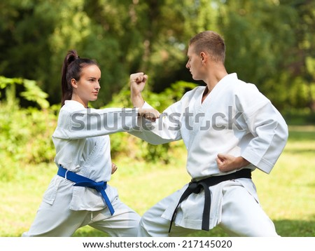 Young couple doing Martial Arts exercise in nature - stock photo