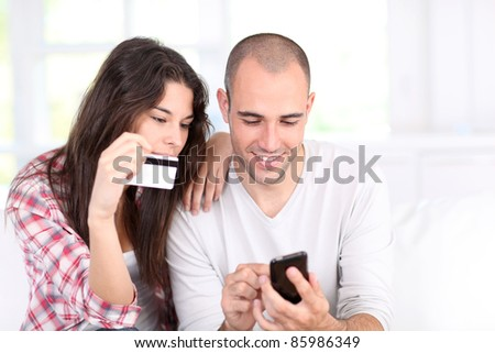 Young couple doing online shopping with smartphone - stock photo