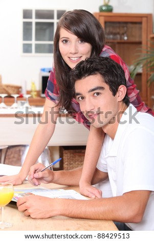 Young couple doing paperwork at the kitchen table