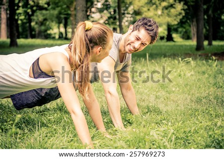 Young couple doing push ups in a park - Two athletes training outdoors