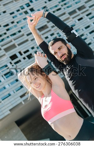 Young couple doing stretching outdoors - stock photo