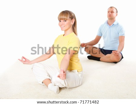 young couple doing yoga exercise together indoors - stock photo