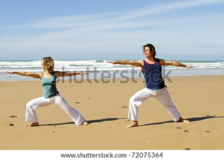 Young couple doing yoga exercises at the beach - stock photo