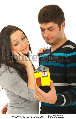 Young couple  dreaming to have a new house and holding a minaiture home in their hands isolated on white background